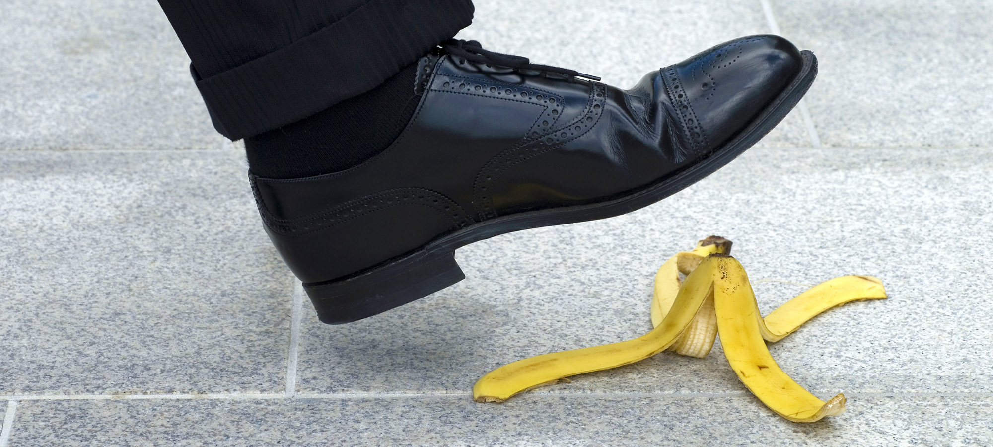 Man with dress shoe about to step on banana peel