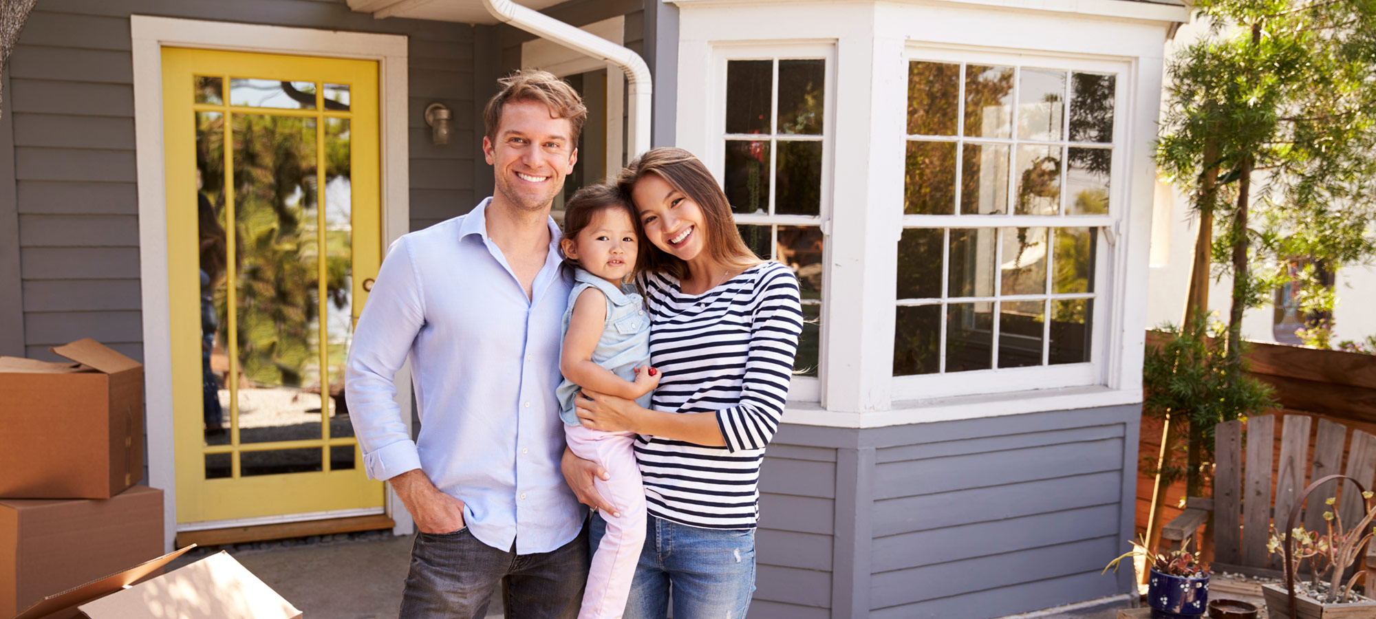 New Homeowners with child, unpacking in front of house